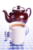 Mug of tea and pot. Full cup of tea and a teapot reflected on checked surface Royalty Free Stock Images