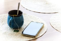 Tea cup and smartphone on kitchen table Royalty Free Stock Photography