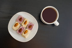 Mug of tea and Turkish Delight with almonds on a plate, top view, black background.  Royalty Free Stock Images