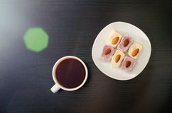 Mug of tea and Turkish Delight with almonds on a saucer, solar flare, top view. Black background Royalty Free Stock Photography