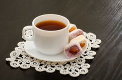 Mug of tea and Turkish delight with nuts on a plate, close-up, black background.  Royalty Free Stock Image