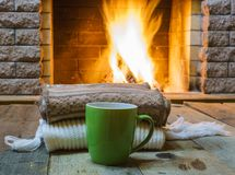 Mug  for tea  and  wool things near cozy fireplace Royalty Free Stock Photography