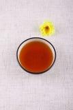 Mug of tea with a yellow flower Stock Photo