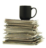 Mug on top of magazine stack Royalty Free Stock Image