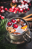 Mug of traditional mulled wine with cranberries, cinnamon sticks and anise star. Close up Royalty Free Stock Photography