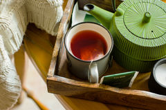 Mug with warm red fruit tea, paper bags, green pot in trey, white knitted sweater hanging over old wooden chair, fall, autumn. Tranquility Stock Images