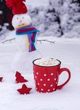 Mug with white polka dots with hot chocolate and marshmallows. Red ceramic mug with white polka dots with hot chocolate and marshmallows, behind a cheerful stock images