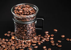 Mug with whole roasted coffee beans Royalty Free Stock Image