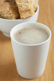 A mugg of coffee with a bowl of rusks in the background. A white mug of coffee with a bowl of rusks in the background Royalty Free Stock Photo