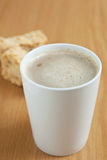 A mugg of coffee with a rusks in the background. A white mug of coffee with rusks in the background Stock Photo