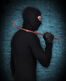 Mugger in mask with nail puller Stock Photo