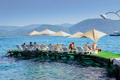 Holiday makers, sitting in a row of deckchairs, enjoying the Summer sun in Akyaka stock image