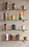Mugs. Display of colorful mugs placed over glass rack Stock Image