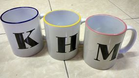 3 Mugs with alphabet. 3 mugs with colors Royalty Free Stock Photography