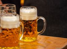 Mugs of beer on a wooden table, closeup view. Oktoberfest, Munich, Bavaria stock photography