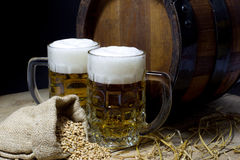 Mugs of Beer, Barrel and Jute Bag Filled with Wheat on Wooden Table Against Black Background Royalty Free Stock Photography