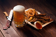 Mugs of beer with snacks Stock Images