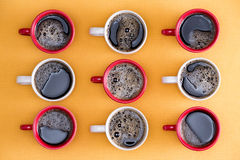 Mugs of black coffee in alternating colors Stock Photos