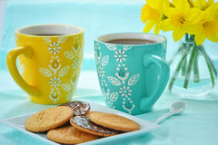 Mugs of coffee with biscuits and daffodils Stock Photo