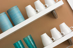 Mugs and cups on the shelf Stock Images