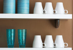 Mugs and cups stored on the shelf. Mugs, cups and jars stored on the shelf Royalty Free Stock Image