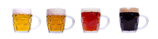 Mugs with different beer in a row Stock Images