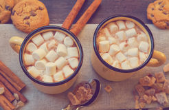 Mugs filled with hot chocolate and marshmallows. Two mugs filled with hot chocolate and marshmallows with cinnamon and brown sugar. Top view. Vintage toned Royalty Free Stock Photography