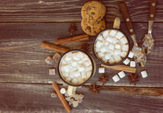 Mugs filled with hot chocolate and marshmallows. Two mugs filled with hot chocolate and marshmallows at the old wooden table with cinnamon and brown sugar. Top Royalty Free Stock Images