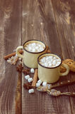 Mugs filled with hot chocolate and marshmallows. Two mugs filled with hot chocolate and marshmallows at the old wooden table with cinnamon and brown sugar Royalty Free Stock Images