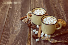 Mugs filled with hot chocolate and marshmallows. Two mugs filled with hot chocolate and marshmallows at the old wooden table with cinnamon and brown sugar Stock Photography