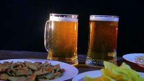 Mugs with foaming light beer on a wooden table against a black background. The average plan stock footage