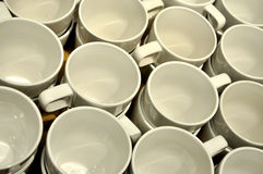 Mugs in formal alignment. Cream colored mugs in formal alignment, shown as pattern, crowd and principle Stock Photography