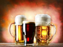 Mugs and glass of beer on a wooden table Royalty Free Stock Image