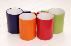 mugs green, orange, blue, red Royalty Free Stock Images