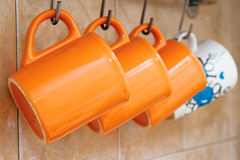 Mugs on hooks. Tea cup orange hang on hooks on the wall Stock Photography