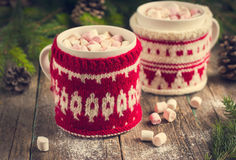 Mugs with hot chocolate and murshmallow, wrapped in a winter kni Royalty Free Stock Image