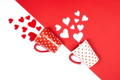Mugs with scattered hearts on red and white stock images