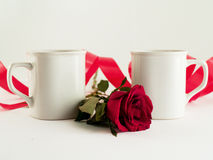Mugs for two. Two white mugs with red rose and ribbon on white background Stock Photography