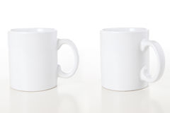 Mugs on White. Two white coffee mugs isolated over a white background royalty free stock images