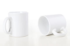 Mugs on White. Two white coffee mugs isolated over a white background stock photos