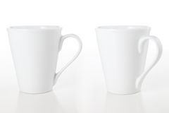 Mugs on White. Two white coffee mugs isolated over a white background stock photography
