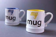 Mugs. Yellow and blue drinking mugs on grey background Royalty Free Stock Photo
