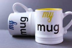 Mugs. Yellow and blue drinking mugs on grey background Royalty Free Stock Photos