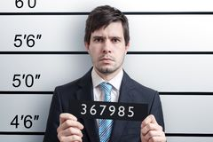 Mugshot of young guilty man at police station.  stock images