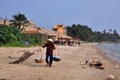 Mui ne fishing village. A Vietnamese street vendor carry her goods In mui ne fishing village stock images