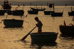 Fisherman Silhouette with Paddle in Round Boat at Sunset Royalty Free Stock Photos