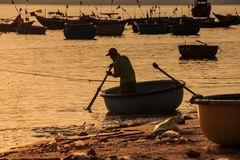Fisherman Silhouette Rows in Round Boat with Paddle at Sunset Royalty Free Stock Image