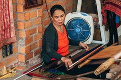 MUI NE, VIETNAM - MARCH 6, 2017: A woman weaver at a traditional loom for yarn silk Stock Photos
