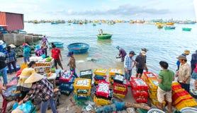 Mui Ne, Vietname, o 23 de abril de 2018: Introduza no mercado a aldeia piscatória adiantada quando os peixes de venda de compra o Imagem de Stock Royalty Free