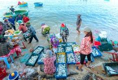 Mui Ne, Vietname, o 23 de abril de 2018: Introduza no mercado a aldeia piscatória adiantada quando os peixes de venda de compra o Fotografia de Stock Royalty Free